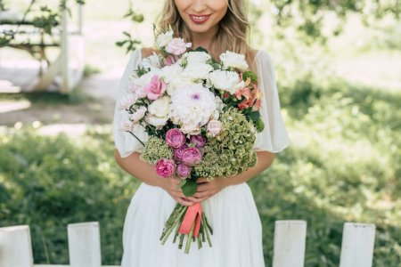 cropped shot of happy blonde bride holding beautiful wedding bouquet outdoors