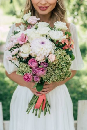 cropped shot of smiling blonde bride holding beautiful wedding bouquet