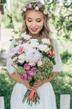 attractive smiling bride in floral wreath holding beautiful bouquet of flowers outdoors