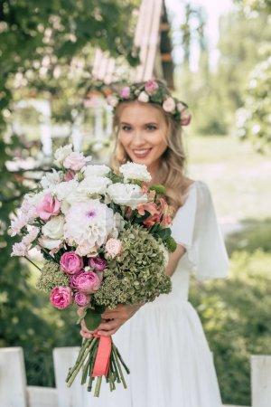 close-up view of happy young bride holding beautiful wedding bouquet outdoors