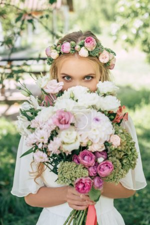 gorgeous blonde bride holding bouquet of flowers and looking at camera