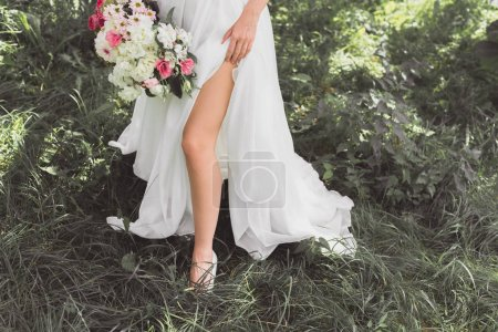 low section of young bride in wedding dress holding bouquet of flowers in garden