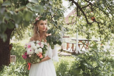 beautiful pensive bride holding wedding bouquet and looking away in garden