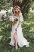 """Постер, картина, фотообои """"Красивая блондинка невеста в свадебное платье и венок Холдинг букет цветов и улыбка на камеру"""""""