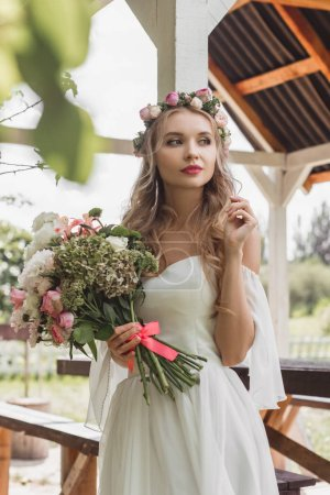 beautiful thoughtful young bride holding bouquet of flowers and looking away