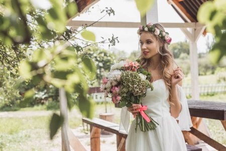 beautiful tender young bride holding wedding bouquet and looking away