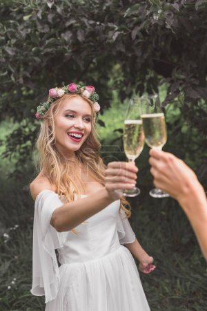 partial view of happy young bride clinking glasses of wine with someone in park