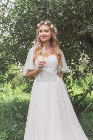 beautiful smiling young bride in floral wreath and wedding dress holding glass of champagne and looking away outdoors