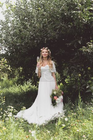 beautiful young bride holding wedding bouquet and glass of champagne, smiling at camera in garden