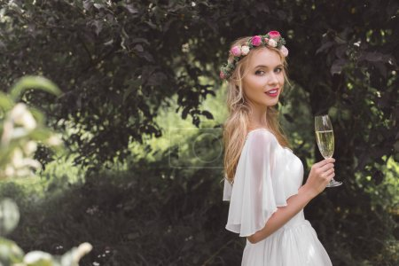 beautiful young bride holding glass of champagne and smiling at camera outdoors