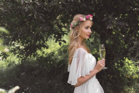 side view of beautiful young bride in floral wreath holding glass of wine outdoors
