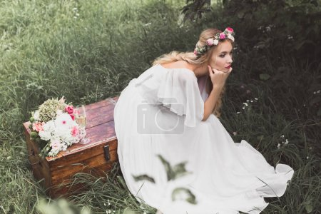 high angle view of beautiful young bride sitting on vintage chest and looking away outdoors