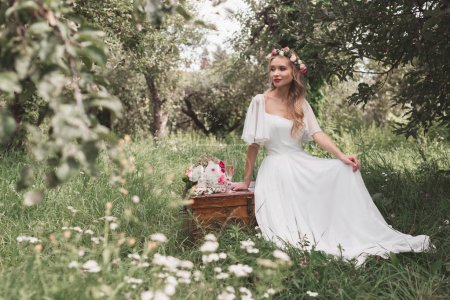 beautiful smiling young bride sitting on wooden chest and looking away in park