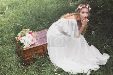 high angle view of beautiful young bride sitting on vintage chest and looking at camera