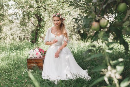 beautiful young bride holding glass of champagne and smiling at camera while sitting on vintage chest in garden