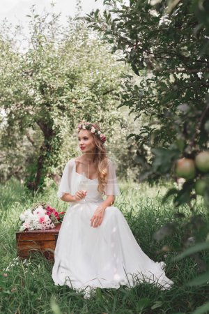 beautiful happy young bride holding glass of wine and sitting on vintage chest in garden