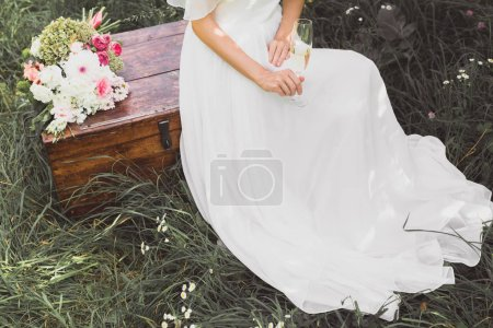 high angle view of bride holding glass of champagne and sitting on vintage chest