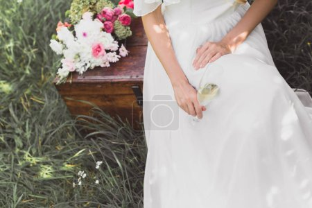 cropped shot of bride holding glass of wine and sitting on vintage chest