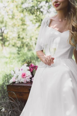 cropped shot of smiling young bride holding glass of champagne and sitting on vintage chest