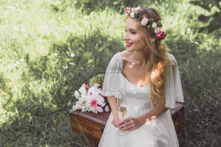 high angle view of smiling young bride holding glass of champagne and sitting on vintage chest