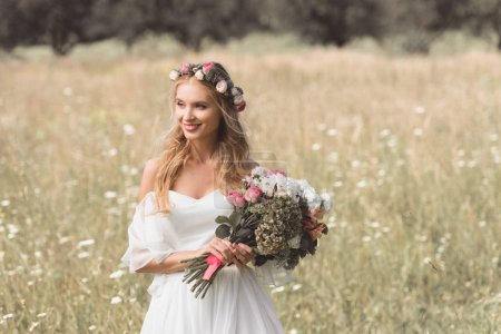 beautiful smiling young bride holding wedding bouquet and looking away outdoors