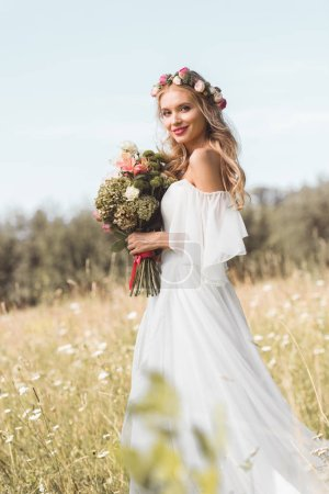 beautiful young bride in wedding dress and floral wreath holding bouquet and smiling at camera