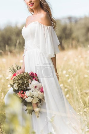 cropped shot of smiling young bride in wedding dress holding bouquet of flowers outdoors
