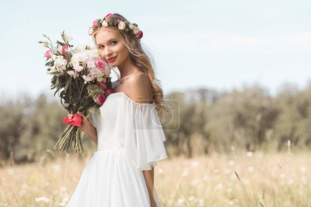 beautiful young bride holding wedding bouquet and smiling at camera outdoors