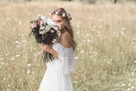 beautiful young bride in floral wreath holding wedding bouquet and looking at camera outdoors
