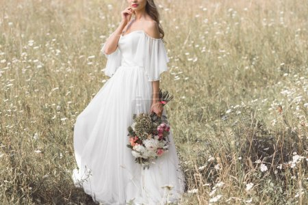 cropped shot of young bride in wedding dress holding bouquet of flowers outdoors