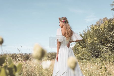 rear view of beautiful young blonde bride walking on beautiful field