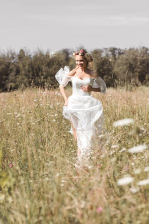 beautiful happy young bride in wedding dress running on field