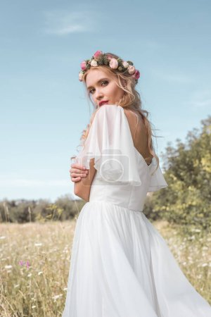 tender young bride in wedding dress and floral wreath standing on field and looking at camera