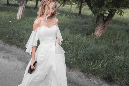 high angle view of upset young bride in wedding dress holding bottle of wine and walking in park