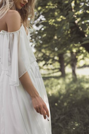 cropped shot of young bride in wedding dress holding cigarette outdoors