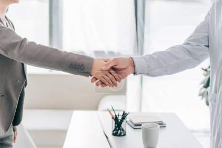 cropped image of patient and doctor shaking hands in clinic
