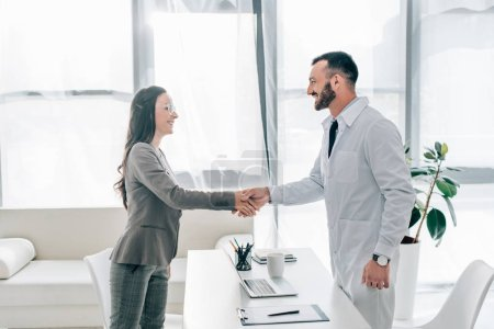 Photo for Side view of smiling patient and doctor shaking hands in clinic - Royalty Free Image
