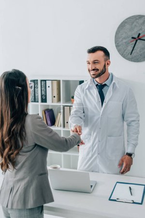 patient and smiling doctor shaking hands in clinic