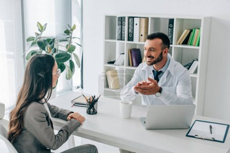 Photo for Patient and smiling doctor talking in clinic - Royalty Free Image