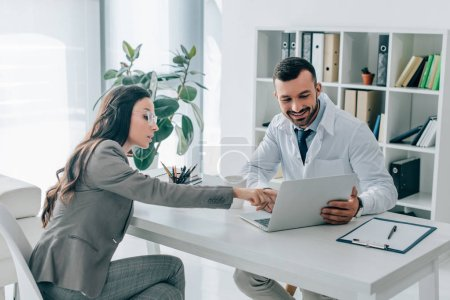 side view of patient pointing on laptop to doctor in clinic
