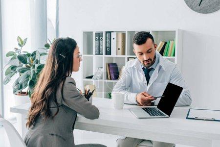 Photo pour Docteur pointant sur ordinateur portable avec écran blanc au patient en clinique - image libre de droit