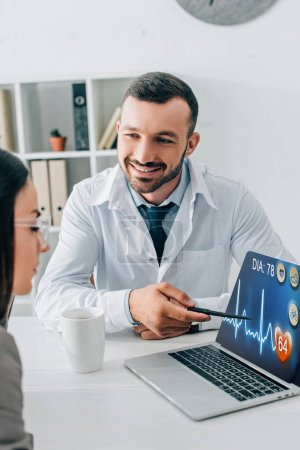 smiling doctor pointing on laptop with medical app to patient in clinic