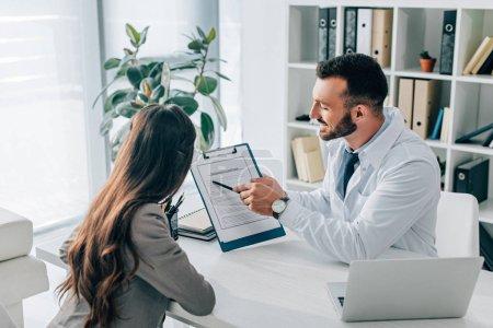 Photo pour Généraliste pointant sur le formulaire de demande d'assurance au patient en clinique - image libre de droit