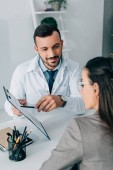 cheerful doctor pointing on insurance claim form to patient in clinic