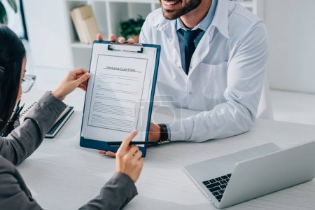 cropped image of smiling doctor showing insurance claim form to patient in clinic