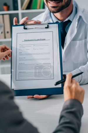 cropped image of doctor showing insurance claim form to patient in clinic