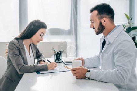 Photo pour Vue latérale du formulaire de déclaration de sinistre signature patients en clinique - image libre de droit