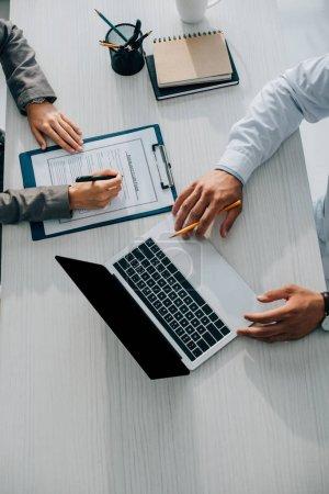Photo pour Image recadrée du patient signant le formulaire de demande de règlement d'assurance à la clinique, médecin utilisant un ordinateur portable - image libre de droit