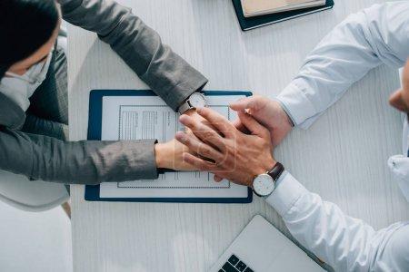Photo pour Vue aérienne du patient et le médecin tenant par la main au-dessus de formulaire de déclaration de sinistre en clinique - image libre de droit