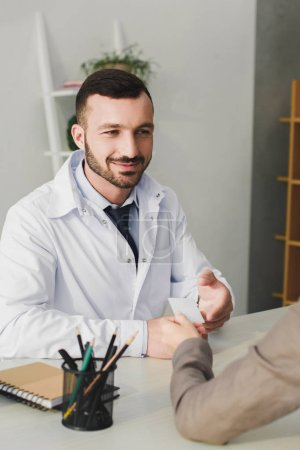 patient giving id card to smiling doctor in clinic